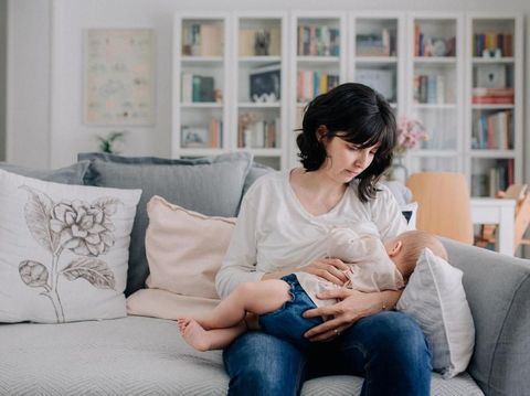 A woman breastfeeds her baby daughter