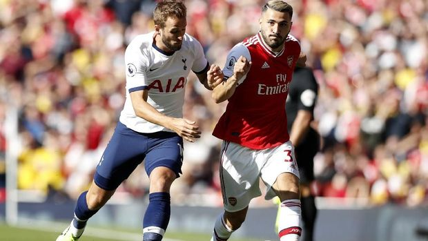 Arsenal's Sead Kolasinac, right, is challenged by Tottenham's Harry Kane during their English Premier League soccer match between Arsenal and Tottenham Hotspur at the Emirates stadium in London, Sunday, Sept. 1, 2019. (AP Photo/Alastair Grant)