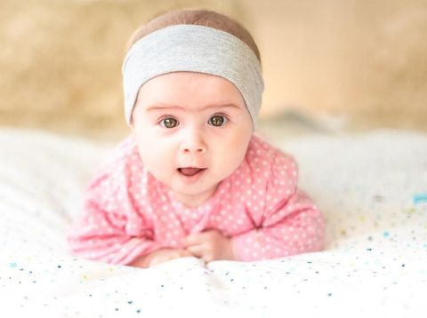 Adorable baby girl with grey headband looking towards camera and smiling. Health concept. 6 months old baby