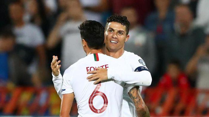 Cristiano Ronaldo diledek Robbie Keane. (Marko Djurica/Reuters)