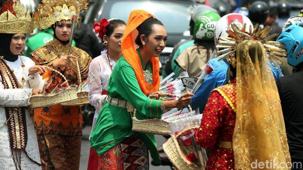 Dukung Revisi UU KPK, Massa Berpakaian Adat Bagikan Bunga