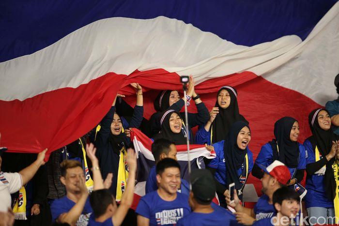 Pendukung Thailand membentangkan bendera raksasa saat menyaksikan pertandingan.