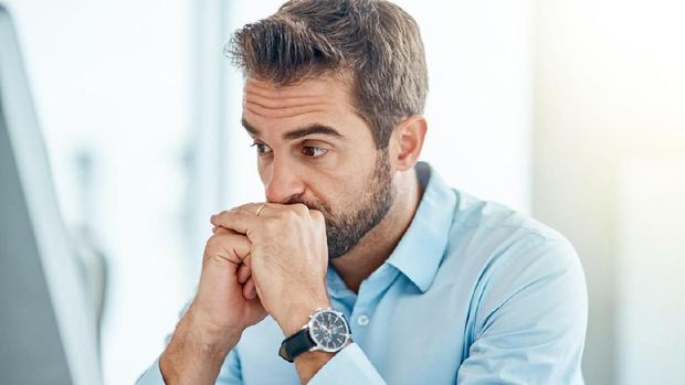 Shot of a young businessman looking anxious while working on a computer in an office