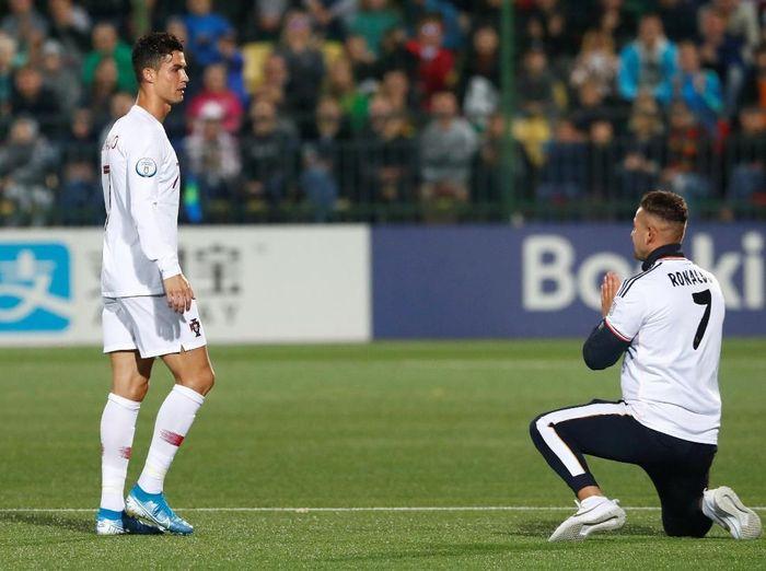 Fans Lithuania berlutut di depan Cristiano Ronaldo, saat striker Portugal itu ditarik keluar dari laga melawan Lithuania di Stadion LFF, Rabu (11/9) dini hari WIB. (Foto: Ints Kalnins/REUTERS)