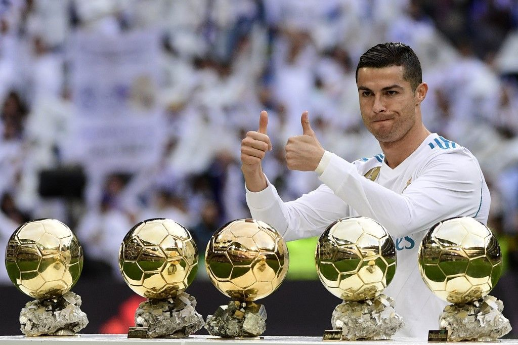 Real Madrid's Portuguese forward Cristiano Ronaldo poses with his five Ballon d'Or trophies ahead of the Spanish league football match between Real Madrid and Sevilla at the Santiago Bernabeu Stadium in Madrid on December 9, 2017. (Photo by PIERRE-PHILIPPE MARCOU / AFP)