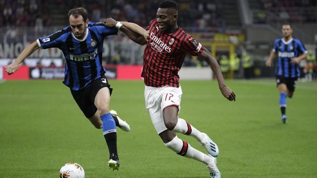 Inter Milan's Diego Godin, left, vies for the ball with AC Milan's Rafael Leao during a Serie A soccer match between AC Milan and Inter Milan, at the San Siro stadium in Milan, Italy, Saturday, Sept.21, 2019. (AP Photo/Luca Bruno)