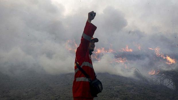 Petugas gabungan dari TNI dan Manggala Agni Daops Banyuasin  berusaha memadamkan kebakaran lahan di Desa Pemulutan, Ogan Ilir, Sumatera Selatan, Jumat (23/8/2019). Berdasarkan data dari Badan Penanggulangan Bencana Daerah (BPBD) Provinsi Sumatera Selatan periode Januari-Agustus sebanyak 1.675,80 hektare lahan yang terbakar di Kab/Kota yang ada di Provinsi Sumsel. ANTARA FOTO/Nova Wahyudi/nz