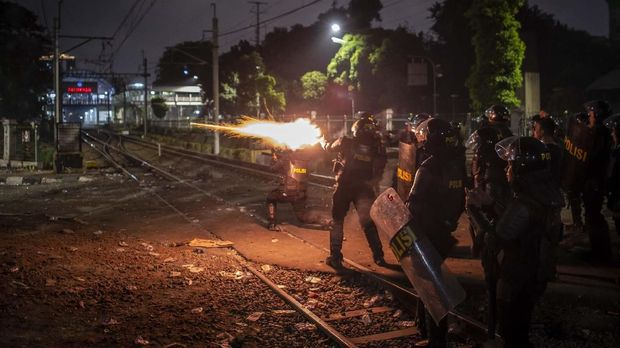 Polisi menembakkan gas air mata untuk membubarkan demonstran 25 September.