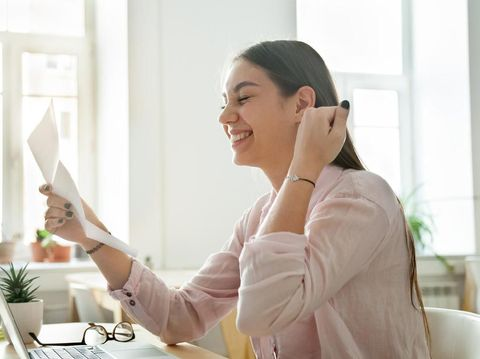 Happy young woman reading good news in paper letter, excited female student or employee receiving positive notification, successful exam results, deal, celebrating success or opportunity, new job