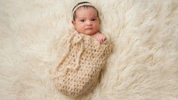 One month old baby girl swaddled in a beige wrap. Shot in the studio on a white blanket.