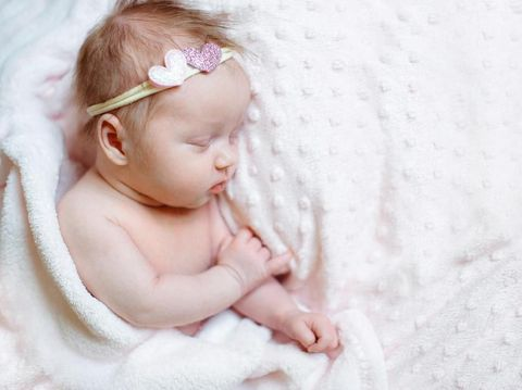Newborn baby girl sleeping in a basket. Concept shooting newborns, innocence.