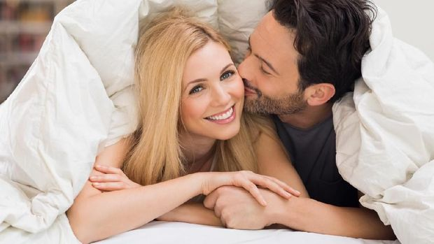 Handsome man kissing woman on cheek under a duvet in the bed. Happy young couple lying down comfortably in their bed at home. Young couple having fun lying on bed at home.
