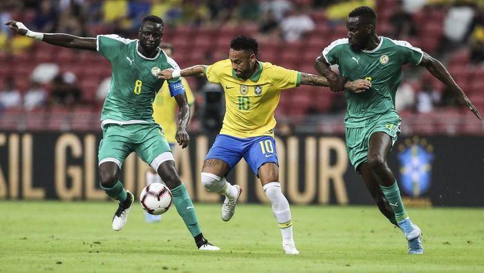 Aksi pemain Brasil, Neymar (tengah), dikepung dua pemain Senegal dalam laga persahabatan di Stadion Nasional, Singapura, Kamis (10/10/2019). Laga berakhir 1-1. (Foto: Danial Hakim/AP Photo)