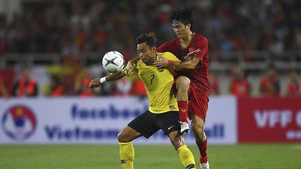 Vietnam's Nguyen Tuan Anh (R) fights for the ball with Malaysia's Mohamad Aidil Zafuan (L) during the Qatar 2022 World Cup qualifying football match between Vietnam and Malaysia at the My Dinh stadium in Hanoi on October 10, 2019. (Photo by Manan VATSYAYANA / AFP)