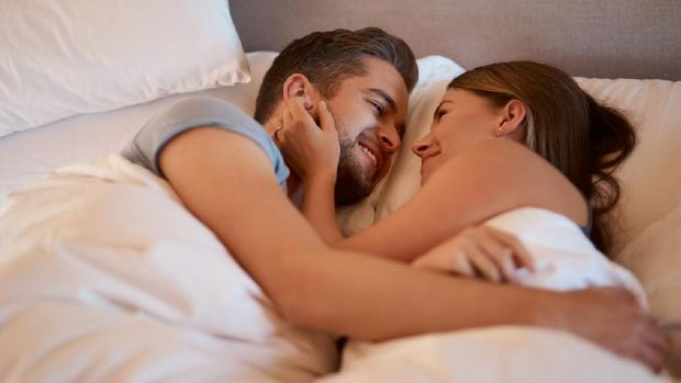 Top view of beautiful happy young couple lying on bed and hugging