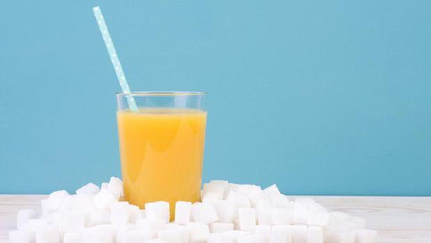Glass of orange juice with plenty of sugar cubes