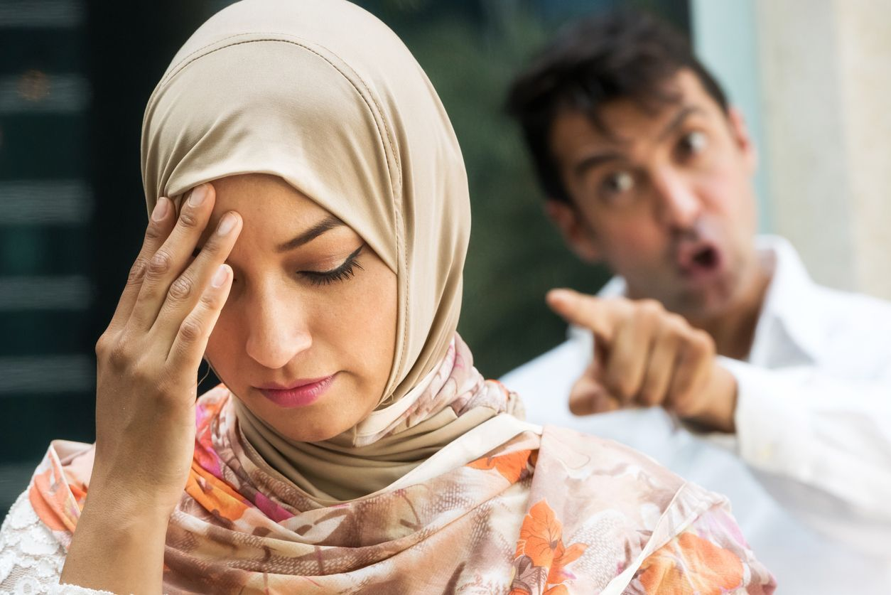 serious muslim woman and a very upset man in the background, they're arguing