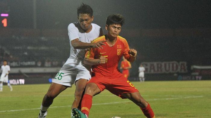 Serdy Fano Boky sedang berebut bola dengan pemain China U-19.  (Nyoman Budhiana/Antara)