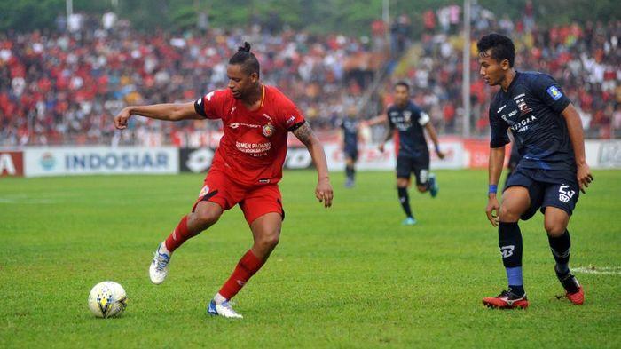 Pesepakbola Semen Padang FC, Vanderlei Francisco (kiri) menggiring bola dibayangi pemain Madura United, Kadek Raditya (kanan). (Iggoy el Fitra/Antara)