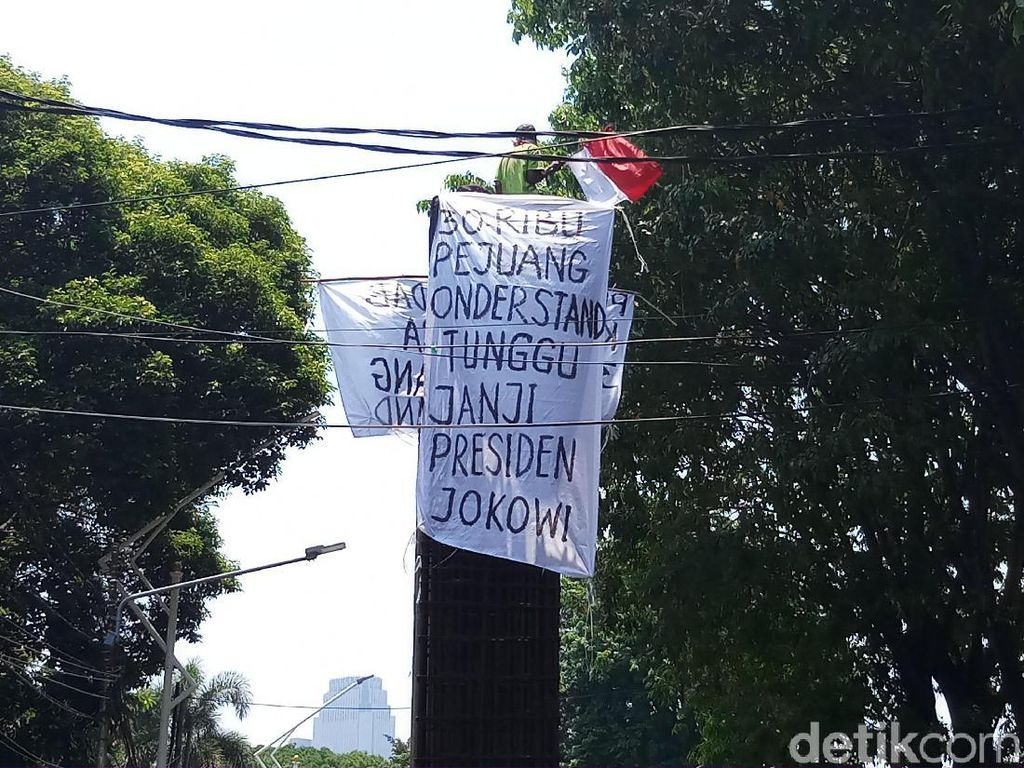 Pria Ini Panjat Beton di Belakang DPR, Kibarkan Spanduk Tagih Janji Jokowi
