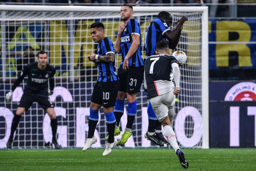 Juventus' Portuguese forward Cristiano Ronaldo (Front R) shoots a free kick during the Italian Serie A football match Inter vs Juventus on October 6, 2019 at the San Siro stadium in Milan. (Photo by Alberto PIZZOLI / AFP)