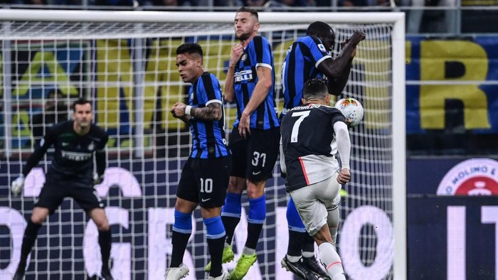 Juventus Portuguese forward Cristiano Ronaldo (Front R) shoots a free kick during the Italian Serie A football match Inter vs Juventus on October 6, 2019 at the San Siro stadium in Milan. (Photo by Alberto PIZZOLI / AFP)