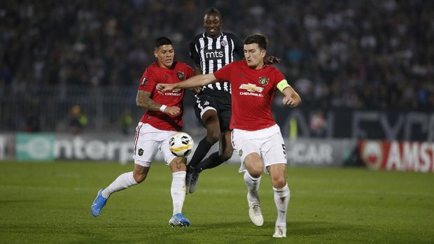 Partizan's Umar Sadiq, center, tries to get past Manchester United's Marcos Rojo, left, and Harry Maguire during their Europa League group L soccer match at the Partizan stadium in Belgrade, Serbia, Thursday, Oct. 24, 2019. (AP Photo/Marko Drobnjakovic)