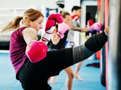 A group of women kickboxing and training together at their local gym.