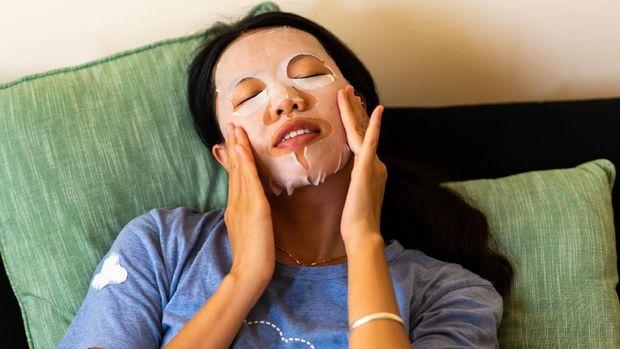 Asian woman applying face mask at home