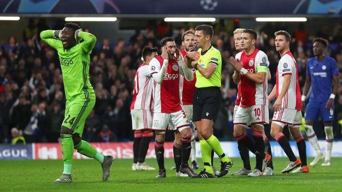 Para pemain Ajax Amsterdam memperotes keputusan wasit yang memberi kartu merah untuk Joel Veltman (Foto: Catherine Ivill/Getty Images)