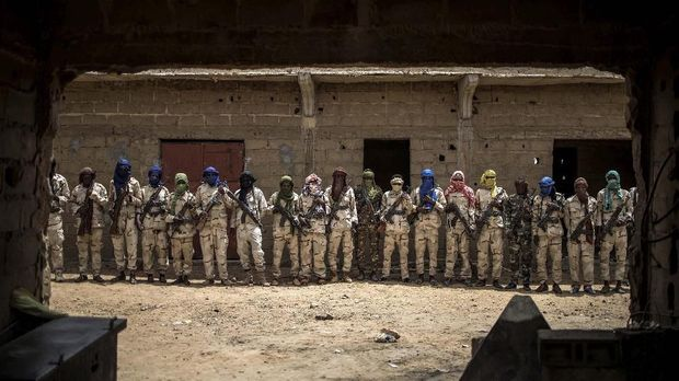 A group of Fulani militiamen pose for a picture with their weapons on July 6, 2019, at an informal demobilisation camp in Sevare run by Sekou Bolly, a local Fulani businessman whose goal is to take away young Fulani from the morse of jihadism. (Photo by Marco LONGARI / AFP)