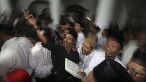 Jamaah membaca sholawat nabi saat tradisi berebut koin di masjid Jami Jamsaren, Kota Kediri, Jawa Timur, Jumat (8/11/2019) malam. Tradisi pembacaan sholawat nabi yang disertai dengan melempar dan berebut uang logam tersebut guna memperingati Maulid Nabi Muhammad SAW. ANTARA FOTO/Prasetia Fauzani