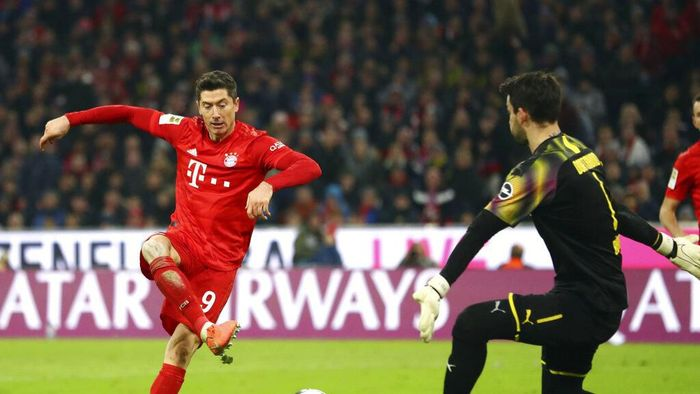 Bayerns Robert Lewandowski, right, scores his sides opening goal during the German Bundesliga soccer match between FC Bayern Munich and Borussia Dortmund, in Munich, Germany, Saturday, Nov. 9, 2019. (AP Photo/Matthias Schrader)