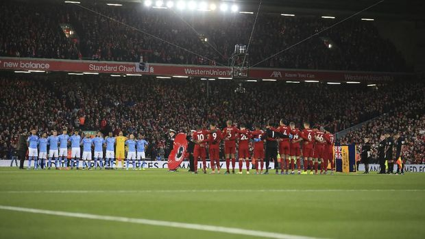 Manchester City and Liverpool teams stand for a minute of silence for the Remembrance Day, during the English Premier League soccer match between Liverpool and Manchester City at Anfield stadium in Liverpool, England, Sunday, Nov. 10, 2019. (AP Photo/Jon Super)