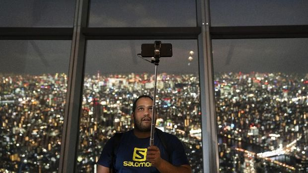 Chandre Groenewald, visiting from South Africa, uses a selfie stick to photograph himself with a view of the cityscape of Tokyo at Tokyo Skytree's observation deck Thursday, Sept. 26, 2019, in Tokyo. The Skytree is the tallest tower in the world. (AP Photo/Jae C. Hong)