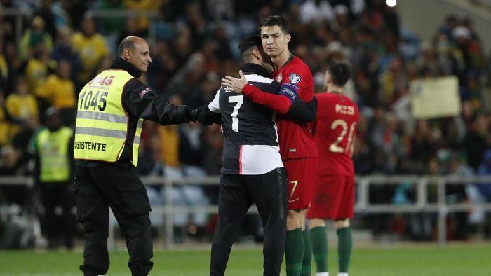 Cristiano Ronaldo memeluk penyusup di laga timnas Portugal dengan Lithuania. (Armando Franca/AP Photo)
