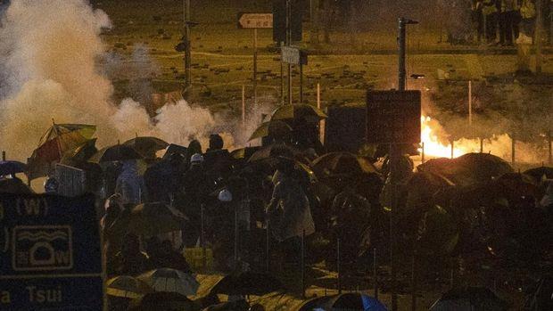 Demonstran Hong Kong berlindung dari gas air mata yang ditembakkan polisi
