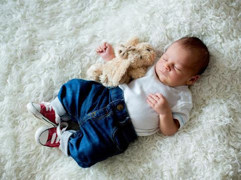 Fashionable little newborn baby boy, sleeping in the afternoon at home in bed with cute toy