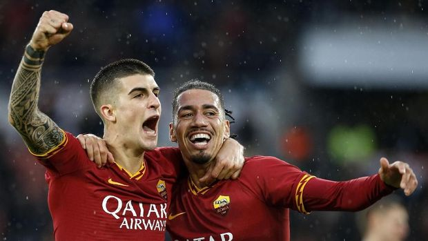 Roma's Gianluca Mancini, left, celebrates with his teammate Chris Smalling after scoring his side's second goal, during the Serie A soccer match between Roma and Bresciaat the Olympic stadium stadium in Rome, Sunday, Nov. 24, 2019. (Riccardo Antimiani/ANSA via AP)