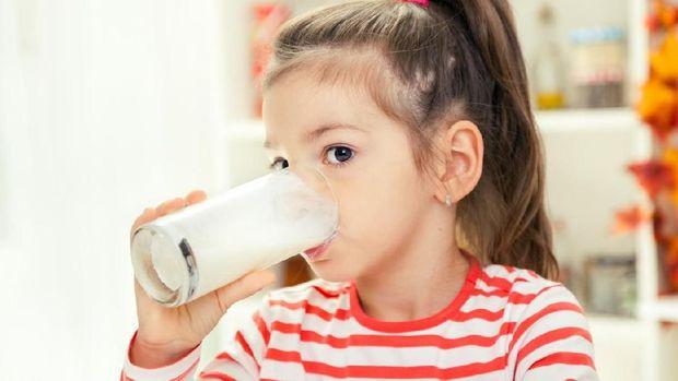 Beautiful Little Girl Drinking Glass of Milk