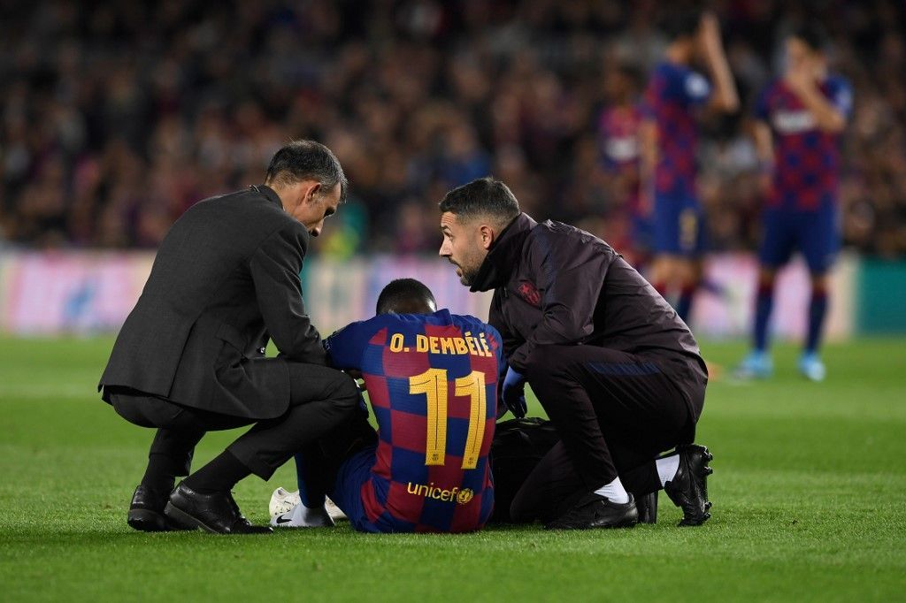 Barcelona's French forward Ousmane Dembele sits on the ground after an injury during the UEFA Champions League Group F football match between FC Barcelona and Borussia Dortmund at the Camp Nou stadium in Barcelona, on November 27, 2019. (Photo by Josep LAGO / AFP)