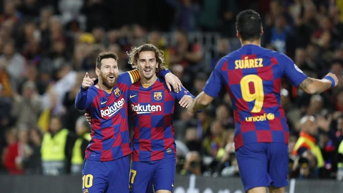Barcelonas Lionel Messi, left, celebrates after scoring his sides second goal with Antoine Griezmann, centre and Luis Suarez during a Champions League soccer match Group F between Barcelona and Dortmund at the Camp Nou stadium in Barcelona, Spain, Wednesday, Nov. 27, 2019. (AP Photo/Joan Monfort)