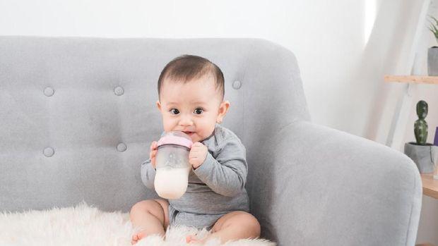A Pretty baby girl drinks water from bottle lying on bed. Child weared diaper in nursery room.