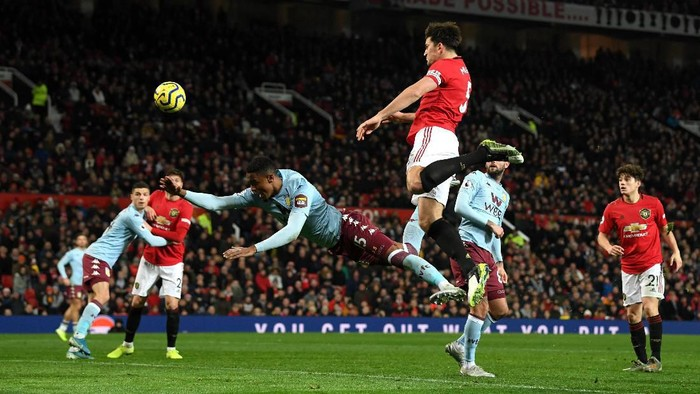 MANCHESTER, ENGLAND - DECEMBER 01: Ezri Konsa Ngoyo of Aston Villa collides with Harry Maguire of Manchester United as he heads the ball towards the goal but misses during the Premier League match between Manchester United and Aston Villa at Old Trafford on December 01, 2019 in Manchester, United Kingdom. (Photo by Stu Forster/Getty Images)