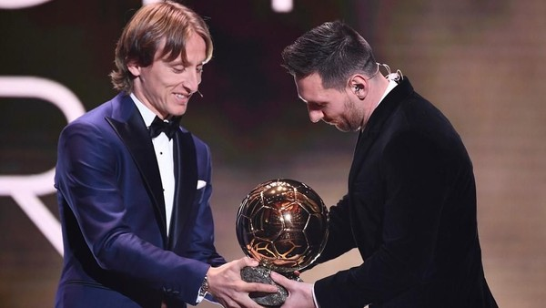 Luka Modric menyerahkan trofi Ballon dOr kepada Lionel Messi (Foto: FRANCK FIFE / AFP)