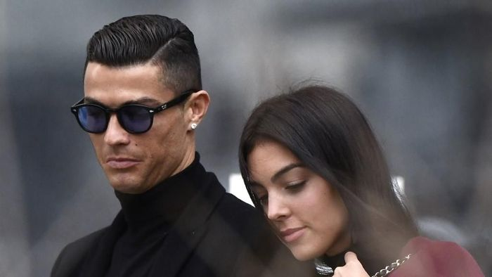 Juventus forward and former Real Madrid player Cristiano Ronaldo leaves with his Spanish girlfriend Georgina Rodriguez after attending a court hearing for tax evasion in Madrid on January 22, 2019. - Ronaldo is expected to be given a hefty fine after Spanish tax authorities and the players advisors made a deal to settle claims he hid income generated from image rights when he played for Real Madrid. (Photo by OSCAR DEL POZO / AFP)