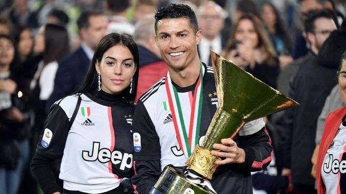 Juventus Portuguese forward Cristiano Ronaldo holds the Italian Champions trophy next to his wife Georgina at the end of the Italian Serie A football match Juventus vs Atalanta on May 19, 2019 at the Allianz stadium in Turin. (Photo by Marco Bertorello / AFP)