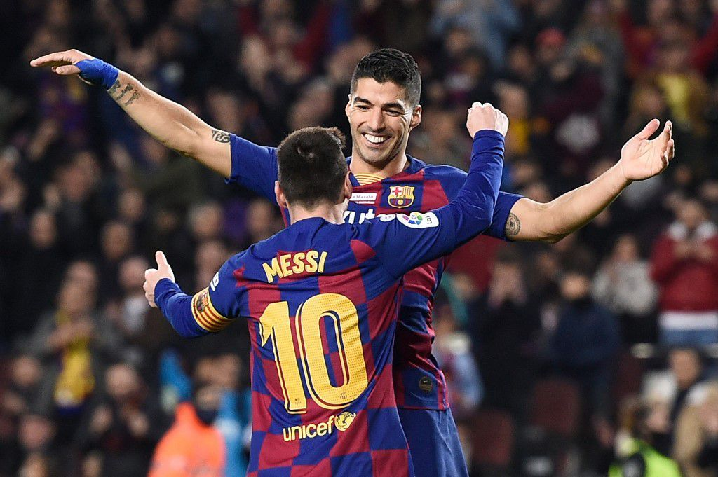 Barcelona's Argentine forward Lionel Messi celebrates his third goal with Barcelona's Uruguayan forward Luis Suarez during the Spanish League football match between FC Barcelona and RCD Mallorca at the Camp Nou stadium in Barcelona on December 7, 2019. (Photo by Josep LAGO / AFP)