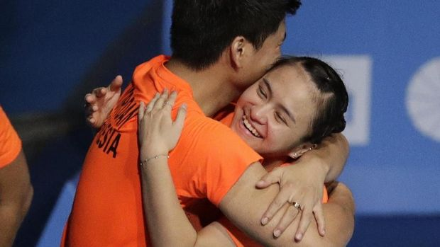Indonesia's Melati Daeva Oktavianti, right, and Jordan Praveen embrace after winning gold during their mixed doubles badminton finals match against Malaysia at the 30th South East Asian Games in Muntinlupa, south of Manila, Philippines on Monday Dec. 9, 2019. (AP Photo/Aaron Favila)