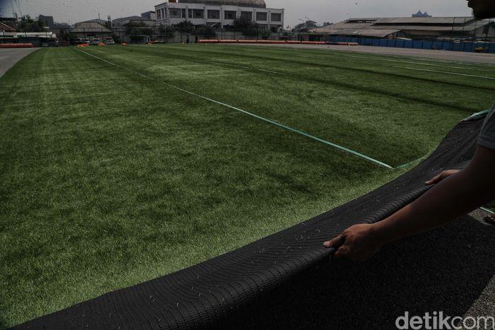 Sejumlah pekerja menyelesaikan pembangunan lapangan sepakbola di kawasan Muara Angke, Jakarta Utara, Senin (9/12).